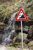 picture of landslide  - Small waterfall running behind a landslide sign outdoors - JPG