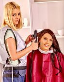 picture of hair curlers  - Woman with long hair at hairdresser with iron hair curler - JPG