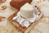 image of deli  - aged italian deli fresh blue stilton cheese and rye ciabatta served on wooden cutting plate on used baking paper as background - JPG