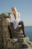 Blonde In A Shirt And Stockings Sitting On A Wall Near Sea