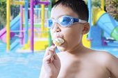 picture of naked children  - Closeup of male child wearing swimming glasses on the pool while enjoying a delicious ice cream - JPG