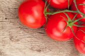 foto of neat  - Bunch of neat red tomatoes on rustic wooden table  - JPG
