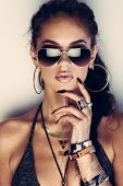 foto of flashing  - Glamorous young woman with flash tattoos in sunglasses - JPG