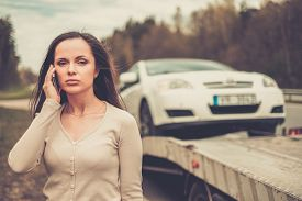 image of towing  - Woman calling while tow truck picking up her car - JPG