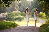 as mulheres correm pelo Parque ensolarado