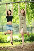Two Beautiful Girls Hanging On Tree Branch In Park, Laughing
