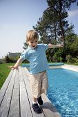 Portrait of a little boy walking beside a pool