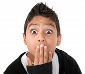 pic of young boy  - Hispanic boy looking shocked with hand on mouth and raised eyebrows - JPG