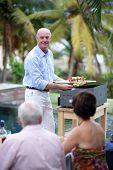 Senior hombre preparar brochetas en una plancha frente a sus amigos