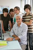 Portrait of a man and a group of teenagers in front of a desktop computer in a classroom
