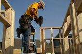 picture of 2x4  - construction worker nailing top of frame to studs using nail gun - JPG
