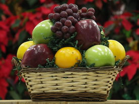 stock photo of gift basket  - fruit basket with red poinsettias as backdrop - JPG
