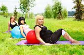 stock photo of pregnancy exercises  - Three pregnant  women relaxing on grass - JPG