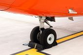 A picture of an orange undercarriage of a business jet standing on the apron