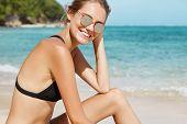 Joyful Positive Female In Swimwear, Dark Glasses Recreats On Sandy Beach, Has Slender Figure, Relaxe poster