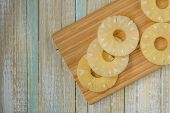 Pineapple Rings Top View. Ananas Slices On A Wooden Board poster