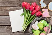 Red tulip flowers bouquet in basket, rabbit cookies and easter eggs on wooden background.  Easter gr poster