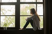 Thoughtful Girl Sitting On Sill Embracing Knees Looking At Window, Sad Depressed Teenager Spending T poster