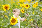 Child In Sunflower Field. Kids With Sunflowers. poster