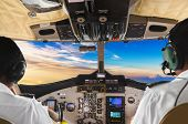 Pilots in the plane cockpit and sunset - transportation background poster