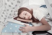 Sleeping Beauty. Pretty Young Long-haired Girl Sleeping On Her Notebooks And Wearing A White T-shirt poster