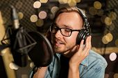 music, show business, people and voice concept - male singer with headphones and microphone singing  poster