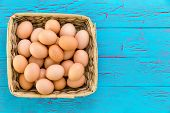 Home Harvested Wicker Basket Of Fresh Nutritious Free Range Brown Eggs In A Rustic Woven Basket Over poster