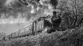 A Black And White Mono Close Up Photograph Of A Steam Train Locomotive And Carriages Smoking And Fro poster