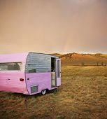 cute vintage camper trailer in the sawtooth mountain range in a desolate camp ground during a summer poster