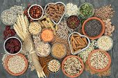 Healthy high fibre dietary food concept with whole wheat pasta, legumes, nuts, seeds, cereals, grain poster