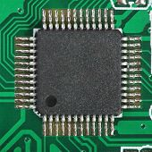 Chip on a green electronic board. Focus on a pins