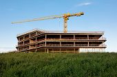 A Construction Crane And A Erected Frame Of The Building Against The Blue Sky. Image Of The Construc poster