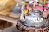 Old Thai Kettle On Thai Charcoal Stove On A Wooden Table Are Thai Traditional Kitchen Style. poster