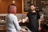 Young Smiling Male Barista Gives Cup Of Coffee To Customer. Young Woman Buy Morning Cup Of Coffee An poster