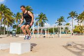Jump box training man atlhete jumping doing strength workout outside in beach calisthenics park in S poster
