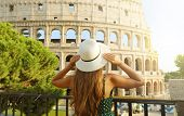Travel In Italy. Back View Of Beautiful Girl Visiting Colosseum Landmark At Sunset In Rome. Summer H poster