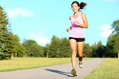 Sport fitness woman running in park on summer day. Asian female runner during outdoor workout. Fit s