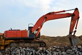 Heavy Excavator Working At Gravel Quarry Unloads Old Concrete Stones For Crushing And Recycling To G poster