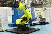 picture of robot  - two big new yellow robots for automotive industry at exhibition - JPG