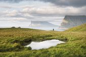 Lonely tourist near small lake looks at foggy islands in Atlantic ocean from Kalsoy island, Faroe Is poster