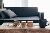 Spring home decor on rustic coffee table over black sofa with cushions. Grey vases and spring flower poster