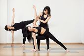 Female Group In Black Sportswear Exercising Yoga. Lesson With Trainer. Standing Yoga Poses Practisin poster