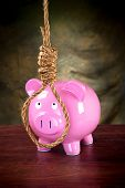 A pink piggybank against a dark, moody background prepared to hang himself with a noose.