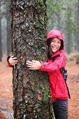 Happy beautiful young woman in an anorak standing hugging a tree in misty woodland as she strives to