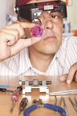 Male jeweler looking through a magnifier to check for flaws in a sapphire.  Focus on sapphire