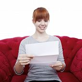 Young Beautiful Red Haired Girl On Red Sofa Reading A Letter In Front Of White Background