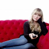 Young Blond Haired Girl On Red Sofa With Remote Control In Front Of White Background