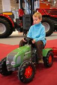 Boy Astride A Small Tractor
