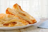 Closeup of two apple turnovers on a plate and granite counter top in a modern diner. Horizontal form