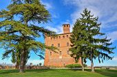 View on red brick ancient castle among trees under blue sky with white clouds in Grinzane cavour, Piedmont, Italy.